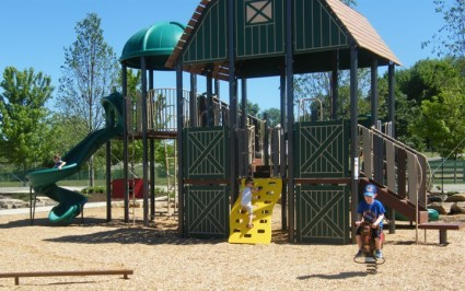 Three kids climbing on Showman's Circle Farm-themed play area at Lake Metroparks Farmpark
