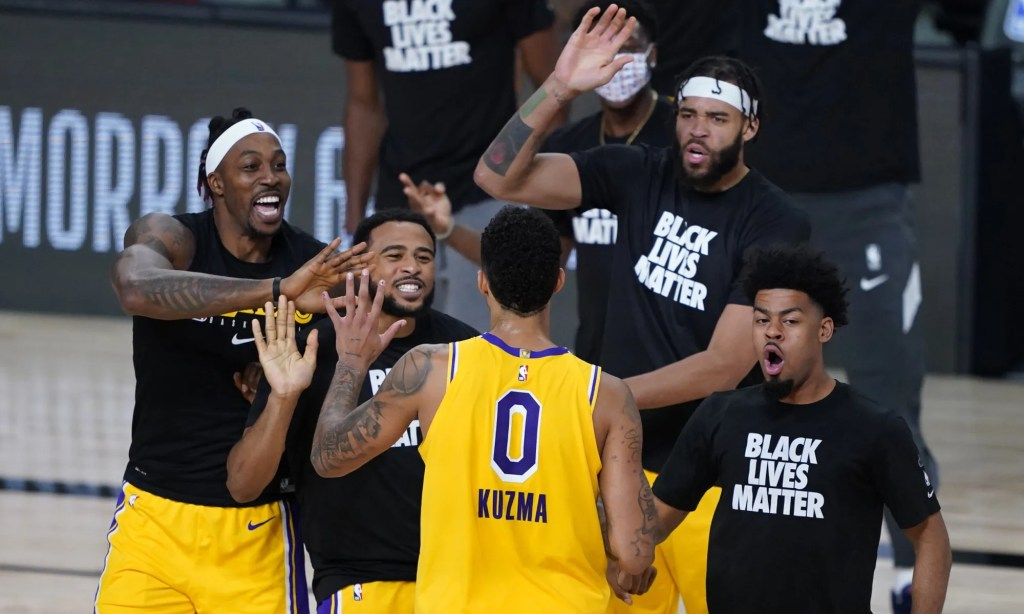 Los Angeles Lakers' Kyle Kuzma (0) is congratulated by teammates after hitting a game-winning 3-pointer against the Denver Nuggets during the second half of an NBA basketball game Monday, Aug. 10, 2020, in Lake Buena Vista, Fla. The Lakers won 124-121.
