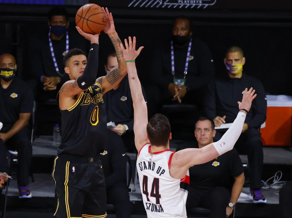 Los Angeles Lakers' Kyle Kuzma (0) shoots a three-point basket against Portland Trail Blazers' Mario Hezonja (44) in Game 4 of an NBA basketball first-round playoff series, Monday, Aug. 24, 2020, in Lake Buena Vista, Fla.