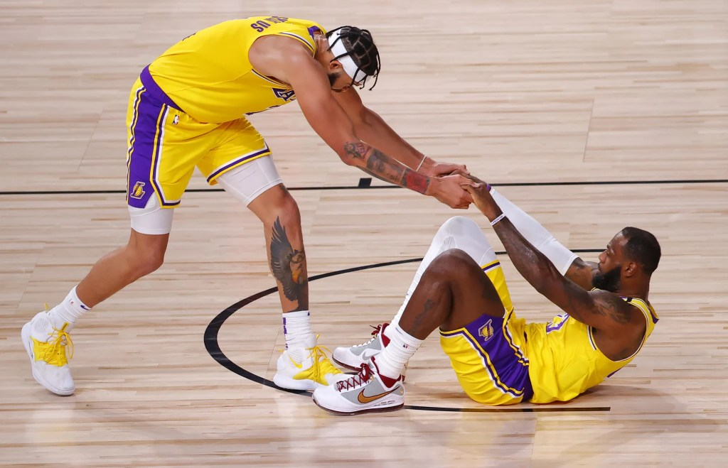 LAKE BUENA VISTA, FLORIDA - AUGUST 20: JaVale McGee #7 of the Los Angeles Lakers helps LeBron James #23 of the Los Angeles Lakers up after a charge against the Portland Trail Blazers in Game Two of the Western Conference First Round during the 2020 NBA Playoffs at AdventHealth Arena at ESPN Wide World Of Sports Complex on August 20, 2020 in Lake Buena Vista, Florida. NOTE TO USER: User expressly acknowledges and agrees that, by downloading and or using this photograph, User is consenting to the terms and conditions of the Getty Images License Agreement.