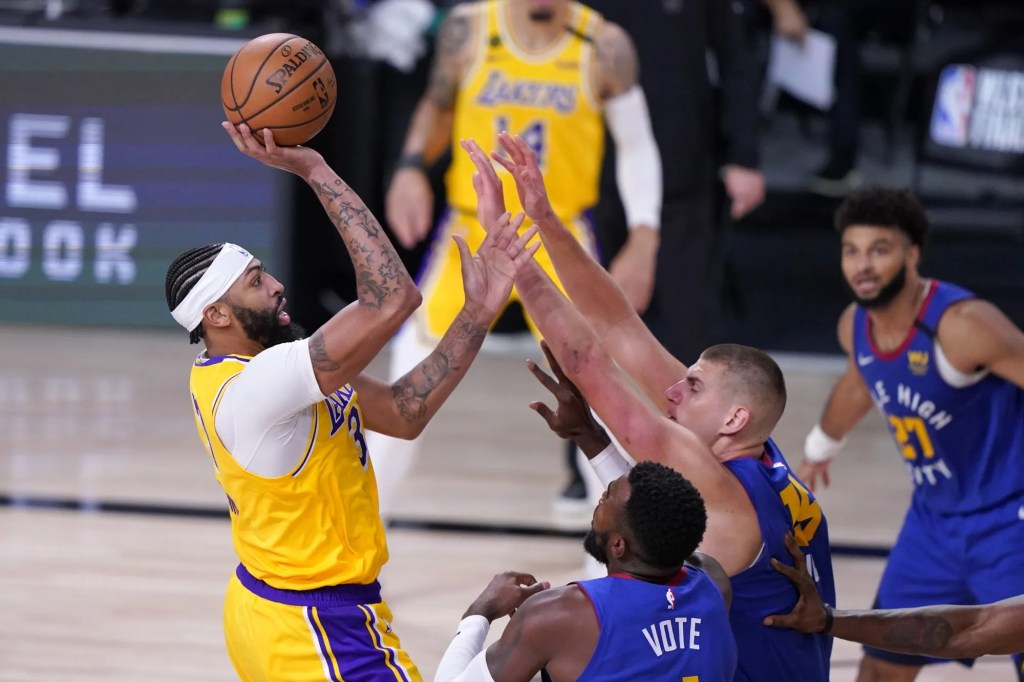 Los Angeles Lakers forward Anthony Davis, left, attempts a shot over Denver Nuggets' Paul Millsap, bottom front, Nikola Jokic, bottom center, and Jamal Murray (27) during the second half an NBA conference final playoff basketball game, Friday, Sept. 18, 2020, in Lake Buena Vista, Fla.