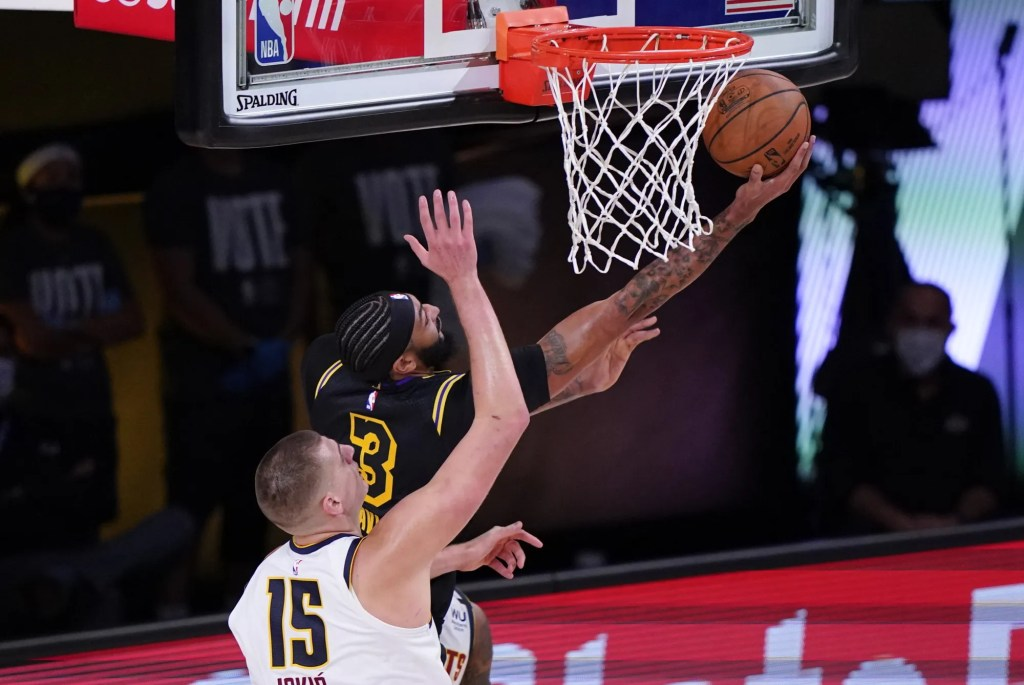 Lakers forward Anthony Davis attempts a reverse layup against Nuggets center Nikola Jokic during Game 2.
