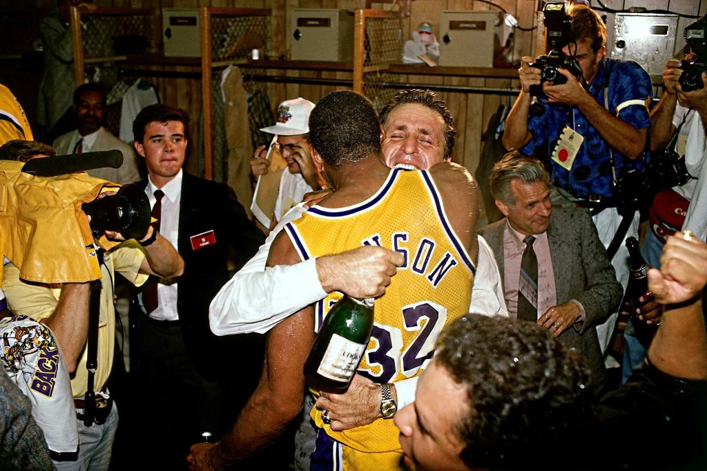 Head Coach Pat Riley of the Los Angeles Lakers hugs 'Magic' Johnson #32 during their locker room celebration after winning the 1988 NBA finals against the Detroit Pistons on June 21, 1988 in Los Angeles, California.
