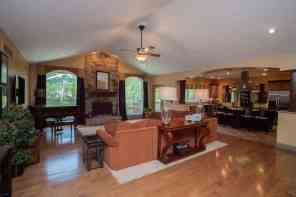 huge vaulted great room w/floor to ceiling stone wood burning fireplace open to kitchen for easy entertaining!