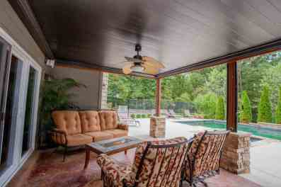 Covered seating on stamped concrete patio features TV hookup