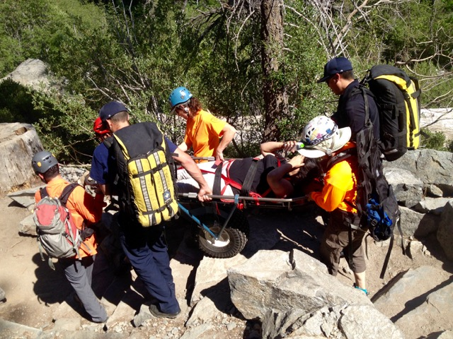 A hiker who suffered a foot injury this summer at Eagle Falls is carried to the trailhead. Photo/Provided