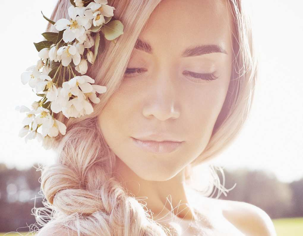 Romantic lady braided hair in wreath of apple trees