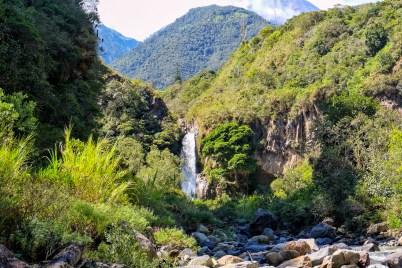 Waterval bij Banos op de route de cascada met vulkaan Tungurahua op de achtergrond