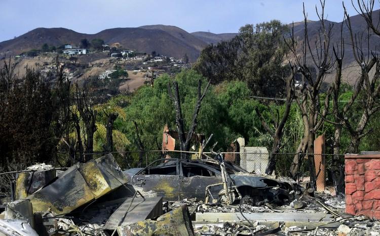 De fondo, algunas casas se ven a salvo, mientras que otras, en primer plano, fueron arrasadas por las llamas
