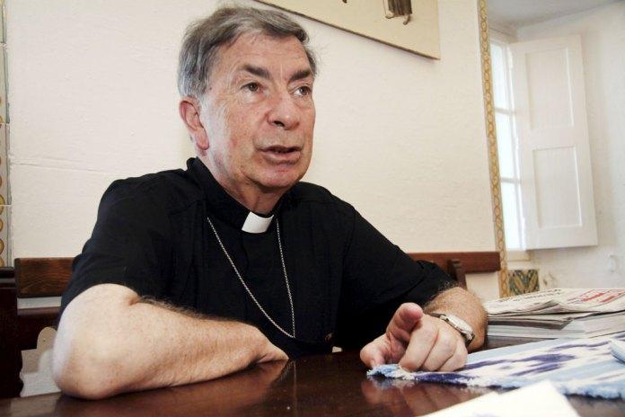 Monseñor Salvador Giménez Valls, obispo de Lleidam sentado tras un escritorio, vestido de negro y concediendo una entrevista.