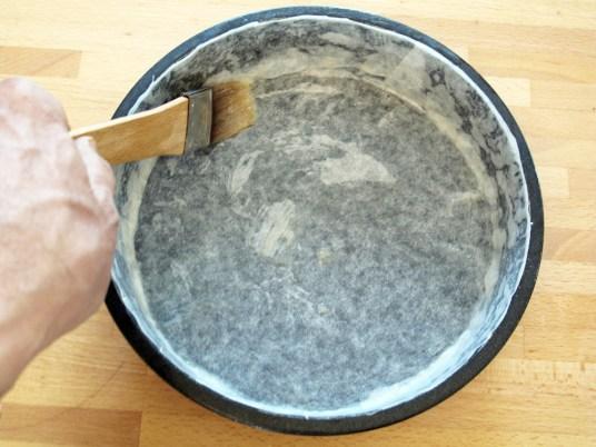 È ora di preparare la tortiera che va foderata con carta da forno per ottenere una superficie della torta perfetta. Ritagliate un disco di carta appena più grande del diametro della tortiera e una o due strisce, alte come il bordo della e lunghe complessivamente come la sua circonferenza. Poi fate sciogliere un po' di burro, intingetevi un pennello da cucina, passate fondo e bordi della tortiera. Posizionate la carta da forno e fissatela ripassandola delicatamente ancora con il burro.