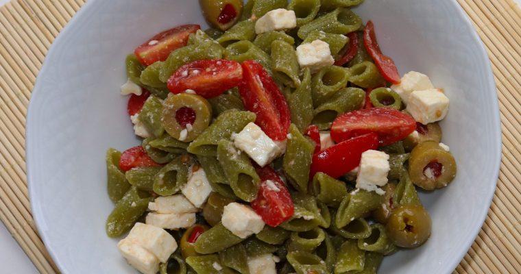 Mezze penne di farina di piselli all'insalata con pomodorini, olive e feta