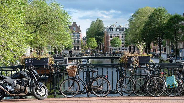 bicis amarradas en un puente que cruza un canal de amsterdam