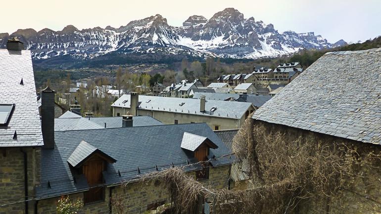 vista de tramacastilla con las montañas al fondo y los tejados de pizarra