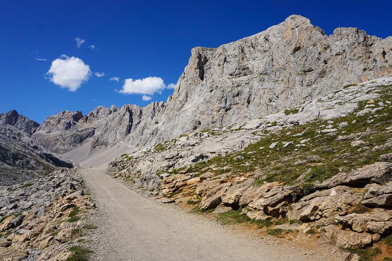 Cielo azul y soleado. Camino de tierra de una de las rutas que se pueden hacer. Montaña y poco verde.