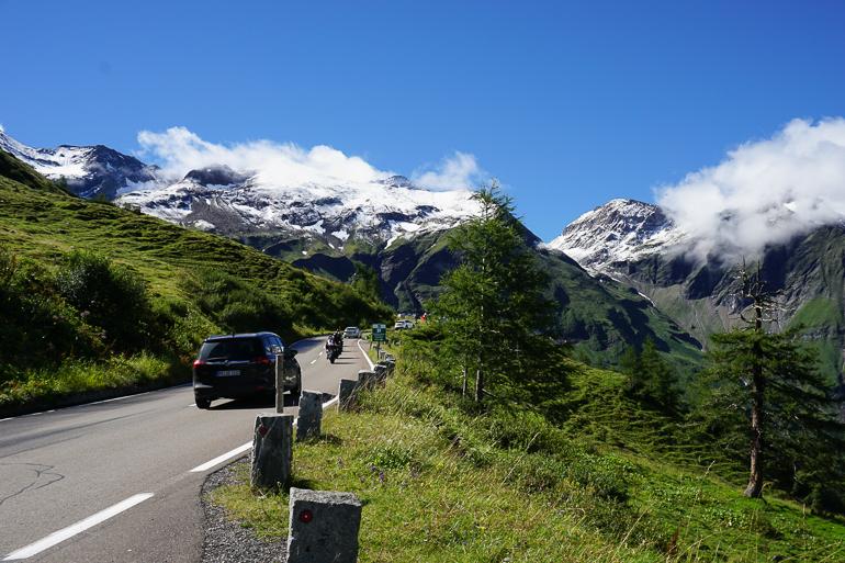 coches circulando por la carretera Grossglockner. alrededor montañas nevadas y campo muy verde