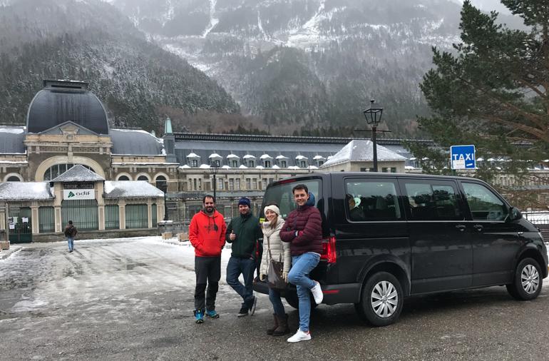 furgoneta y chicos frente a la estacion internacional de canfranc. fondo nevado