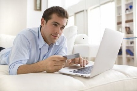 Man using credit card and laptop, shopping online
