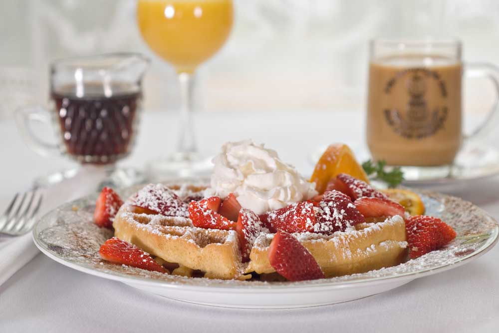 Waffle covered in strawberries and sugar