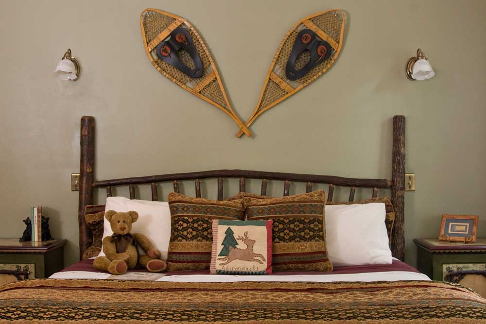 Rustic guest bed with snowshoes on wall
