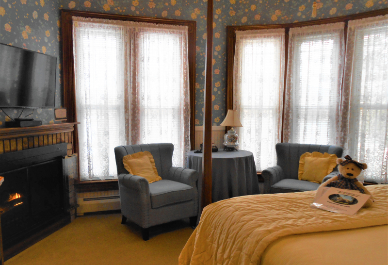 guest room with  flower wallpaper, 2 blue chairs, fireplace and bed