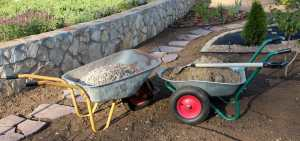 landscaping construction wheelbarrows in front of stone wall