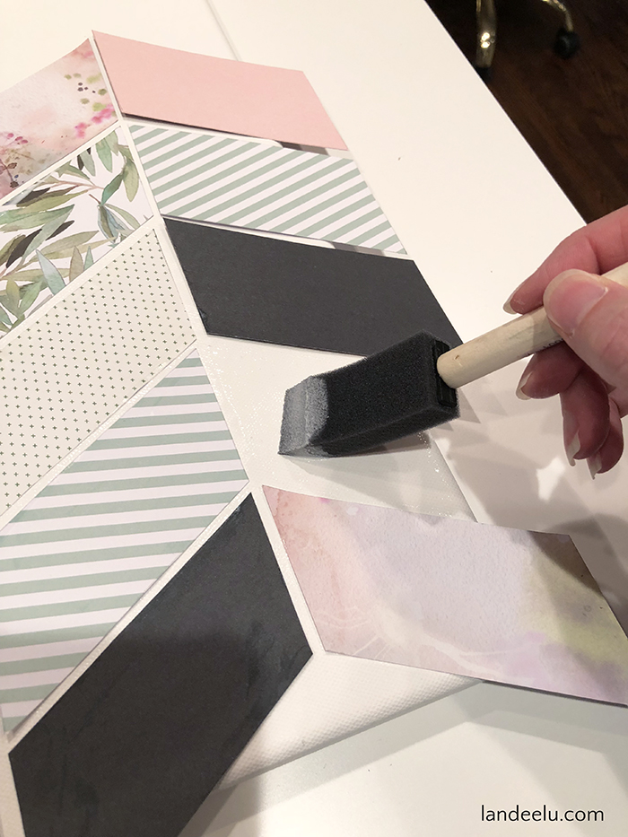 Create this darling herringbone patterned DIY wall decor using decorative papers and mod podge on a blank canvas!