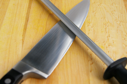 kitchen knife and sharpener on a wooden cutting board © zimmytws - Fotolia.com