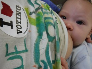 """A baby breastfeeds while mom wears an Ohio """"I voted"""" sticker"""