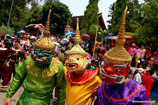 Three people celebrating Lao New Year with traditional masks