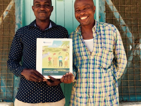 Kenya Land Alliance community facilitators in Tana River, Yusuf Omar Uleta and Odha Ilu Hiyesa, with Namati's new Community Land Protection facilitator's guide. Image courtesy of Namati.