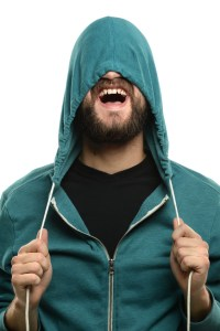 Young man with beard pulling hood over head isolaled over white background