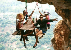 Diners hanging onto a table over a long drop because they are prepared to take a risk