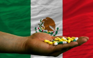man holding capsules in front of complete wavy national flag of mexico symbolizing health, medicine, cure, vitamines and healthy life