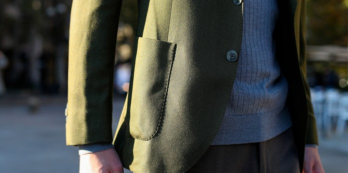 Details of a Lanieri tailored green blazer on a light blue ribbed sweater