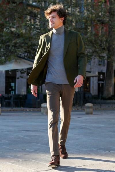 Un uomo indossa blazer verde e pantaloni marroni su misura con maglione dolcevita a coste azzurro
