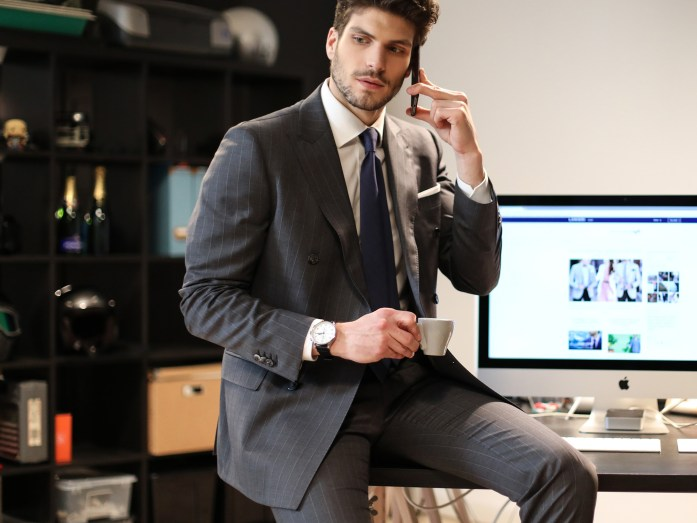 Man on the phone, wearing a office suit office and holding a cup of coffee