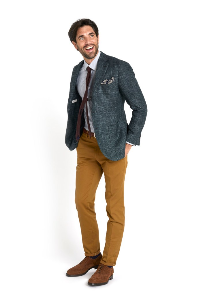 Man wearing blue blazer, striped shirt and brown chinos