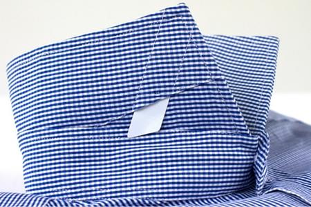 Dettaglio su un colletto di una camicia con stecche bianche in plastica estraibili