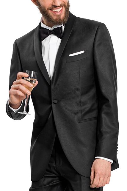 Uomo con flute di champagne indossa uno smoking nero da uomo su misura, camicia bianca, pochette bianca e papillon nero