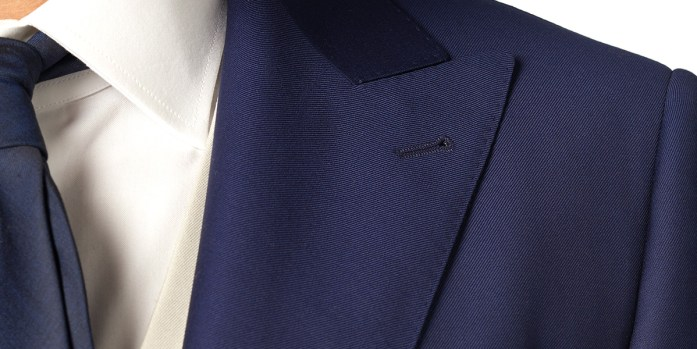 Pointed lapel detail on a two-button blue jacket