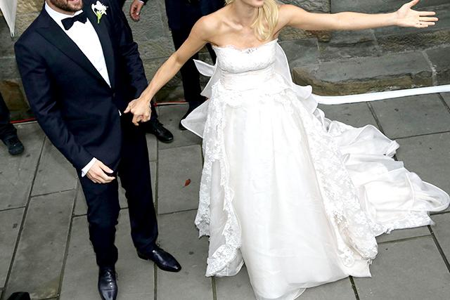 Un uomo indossa uno smoking blu da sposo, accompagnato da una donna in abito da sposa bianco