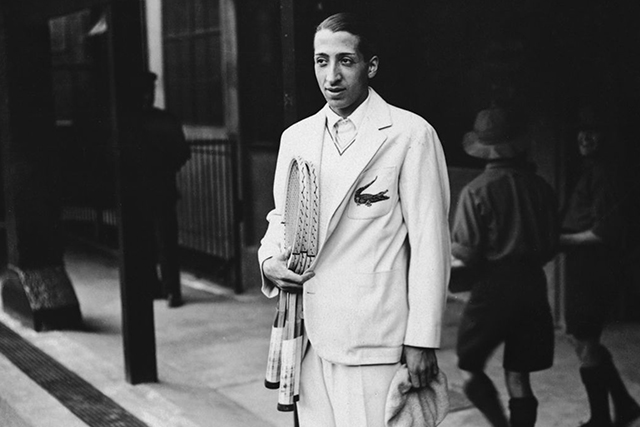 Renè Lacoste wears a white suit over a polo shirt with, wielding two tennis rackets