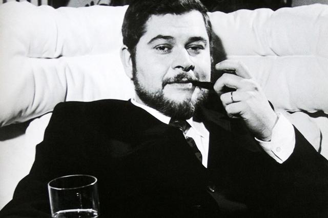 Immagine in bianco e nero di Joe Colombo mentre fuma la pipa