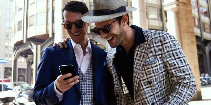 Due uomini indossano completi eleganti e osservano insieme uno smartphone