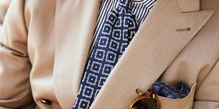 Dettaglio look abito solaro con cravatta fantasia e camicia a righe