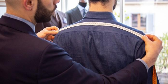 A style advisor taking customers Shoulder width measurements at Lanieri's Atelier