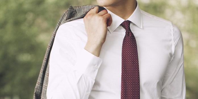 Dettaglio outfit uomo: camicia bianca, cravatta rossa puntinata e giacca grigia in principe di galles sulla spalla.