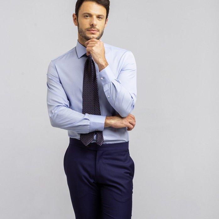 Un uomo indossa una camicia finissimo azzurra, cravatta fantasia blu e pantaloni blu.