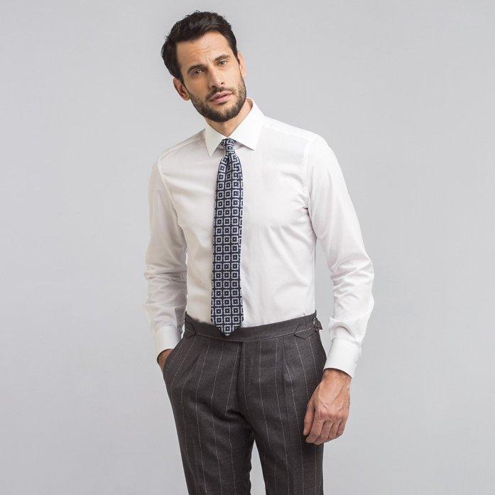Un uomo indossa una camicia icon bianca popeline, cravatta fantasia e pantaloni grigi gessati.